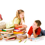 Smart girl lying on top of book piles and talking to cute schoolboy drawing near by