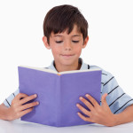 Focused boy reading a book against a white background