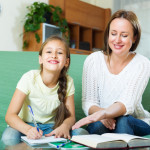 Happy schoolgirl and mother together doing homework at home