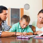 Teenager schoolboy doing homework with parents