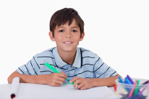Happy boy drawing against a white background