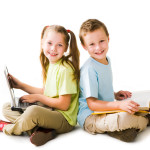 Smart girl with laptop and cute schoolboy with book sitting back to back and looking at camera