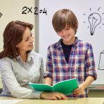 education, elementary school, learning, examination and people concept - school boy holding notebook and teacher in classroom with doodles